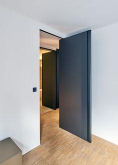 Zwarte pivoterende deur zonder vloerveer of inbouwdelen die vooraf in de vloer ingebouwd dienen te worden.