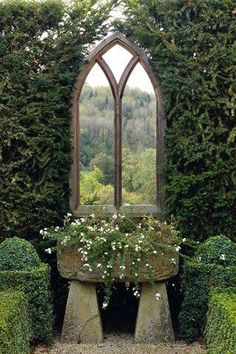 Mirrors aren't just for interiors! Place one on one of your garden walls to create the illusion of a larger space. I love the cathedral look of this one! Image via  House and Garden.