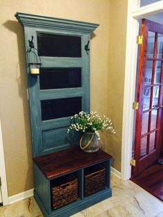 Handcrafted hall tree made with antique door. This hall tree will compliment any entryway, mud room, or laundry room. It will give any room character and function. Door is distressed in antique blue and darker grays. Three top inset panels are in chalkboard for reminders or just fun. Oak bench stained in red mahogany with added storage underneath. Two coat hooks in Venetian bronze. Size varies depending on door. Door in picture is 31 1/2W x 78 1/2H x 19 1/2D. Custom request for alternate…