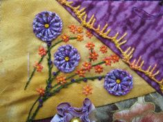 "I ❤ embroidery & crazy quilting . . . TAST week 39: knotted Buttonhole Stitch- A flower spray including Knotted Buttonhole Wheel flowers and Algerian Eye blossoms. In between the ""spokes"" I made straight stitches with two strands of the purple cotton. This flower spray appears on the Juni block of CQJP 2012. ~By Marjolein, of Threads and patches . . ."