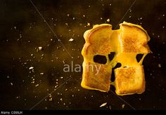 A Grilled Cheese Sandwich cut in four squares pulling the cheese on a wood table. © Francesco Tonelli / Alamy