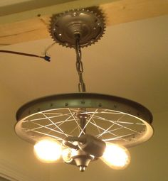 We created this bike rim chandelier from the front wheel of a vintage bike. (13 diameter) It also includes various vintage light fixtures and