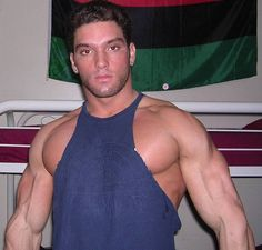 a huge ripped muscle jock posing home gym