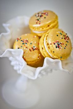 Golden yellow macarons with nonpareils (sprinkles).