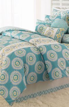 Melodious medallions set off the embellished stripe running down the front of a cotton comforter that reverses to a complementary motif.