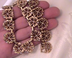 Beautiful late 1940s vintage Trifari necklace. This design carries a design patent filed by Alfred Philippe #154064 and a date of 1949.  This design features gold plate clover flower links that are accented with small clear rhinestone chatons. Closes with a fold over clasp, Signed on the