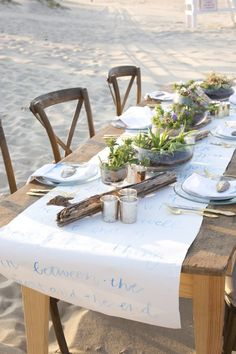 Beach wedding table accented with driftwood and a watercolor lettered paper table runner | Photography - Audra Krieg