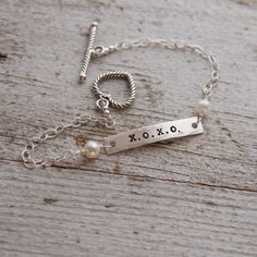 "Hugs and Kisses! XOXO letters are hand stamped into a bar, paired with pearls and skinny chain and finished with a heart shaped toggle clasp.  Total length on this is about 7 3/4"". All metal used in this bracelet is sterling silver. Items ship within 2 weeks and come boxed, ready for gift giving.This design is a copyrighted TheRustedChain original ©. (L-16)"