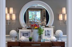art deco console table, collection of white porcelain objects, manzanita branches, wood paneling, metallic accents, and white mirror.