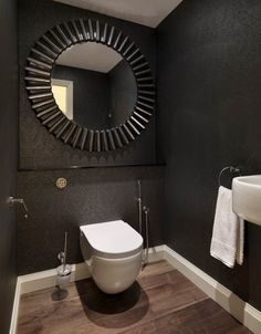 un miroir rond et élégant en noir et un papier peint original et noir dans la salle de bains