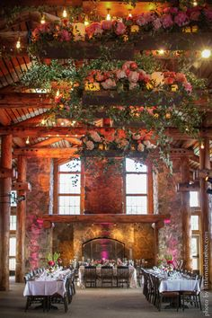"""Chandeliers can be much more than crystals and candles. """"A bride wanted a floral chandelier hanging over the dance floor, so we embellished boards with LED pillar candles and Edison bulbs and topped them with ombré flowers and smilax,"""" says Melony Sebastian of Pink Monkey Solutions."""
