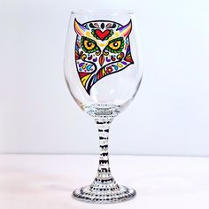 Owl, Wine Glass, Sugar Skull, Single or Set of 2. A colorful Sugar Skull Owl is hand painted on this beautiful wine glass. The design is such that the liquid in the glass will color the skull making for a fun variation in the piece depending on your beverage of choice. The stem and foot of the glass are meticulously dotted using black and white paint. This glass adds a fun touch of color to the dinner table year round. The perfect gift for anyone who collects sugar skulls or owls! Owls…