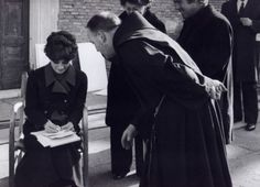 Signora Audrey Hepburn Dotti giving an autograph to a priest and photographed by Guglielmo Coluzzi during a break in the filming of a commercial for UNICEF in Rome (Italy), in January 1972.