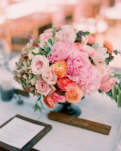 A rustic urn is filled with large succulent plants, peonies, roses, hydrangea, ranunculus, and olive and sage foliage to create a classic arrangement.