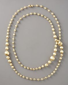 """Long Gold-Bead Necklace  Marco Bicego    This lustrous, subtly textured gold Marco Bicego necklace is a timelessly fresh finishing touch that speaks to a new kind of modern, minimalist opulence. You'll love that the ample length can be doubled to fill scoop and plunging necklines, or draped singly to adorn a high-neck LBD.  Brushed 18-karat yellow gold forms graduated brushed bead stations.  Delicate rolo links.  Approx. 47 1/2""""L.  Lobster clasp.  Made in Italy.    $9,990"""