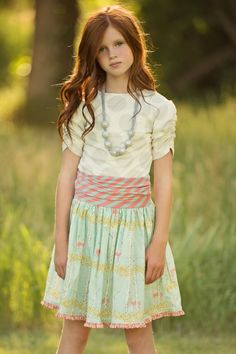 Here's a lovely piece that is a great addition to the Persnickety collection. Its full skirt has a beautiful scene of deer peeking through the trees. The striped ruched waist makes it as comfy as it is stylish. By Persnickety