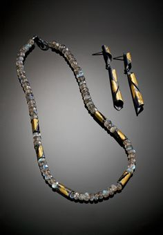 Labradorite Necklace and Midnight Curl Earrings by Judith Neugebauer. In this entrancing necklace, shades of cerulean and turquoise shimmer on the faceted surfaces of labradorite beads, while oxidized sterling silver gleams with 23k gold leaf. Matching earrings are crafted from curls of oxidized sterling silver brushed with 23k gold leaf.