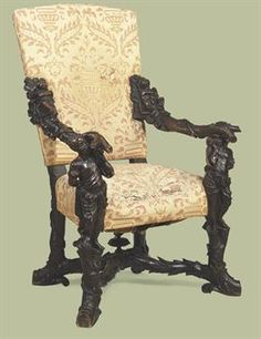 AN ITALIAN CARVED WALNUT CHAIR   IN THE MANNER OF ANDREA BRUSTOLON, LATE 19TH CENTURY   With upholstered back, arms and seat, each arm carved with a blackamoor, on trunk-carved legs joined by a stretcher