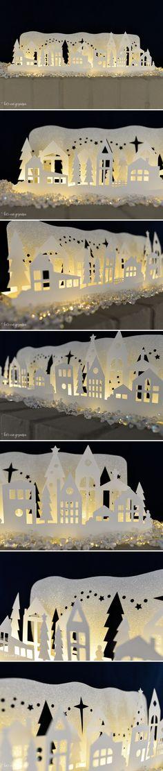 Picture only, no instructions and original done on Cricut: Village de Noël enneigé et illuminé par une mini guirlande électrique. Il mesure 50 cm de long et est constitué de 2 niveaux de papier blanc découpées de maisons, sapins et barrières et d'un fond en vinyle argenté pailleté découpé d'étoiles. Les 3 niveaux de profondeur créent des jeux d'ombres et lumières.