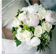 bouquet of white and pale pink peonies, ivory roses, green hydrangea, and green berries.