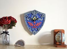 "This beautiful laser engraved clock is hand painted and finished. The clock features the Triforce framed on the iconic Hylian shield made famous by The Ocarina of Time for the N64! If youre buying as a Christmas gift please be advised that the delivery times may be delayed due to seasonal peak.  DIMENSIONS ‾‾‾‾‾‾‾‾‾‾‾‾‾‾‾‾‾‾‾‾‾‾‾‾‾‾‾‾‾‾‾ ↔10"" (25 cm) width ↕ 12"" (30 cm) height  SPECIFICATIONS ‾‾‾‾‾‾‾‾‾‾‾‾‾‾‾‾‾‾‾‾‾‾‾‾‾‾‾‾‾‾‾ ❂ The clock is made from painted MDF ❂ Quartz mechanism is silent…"