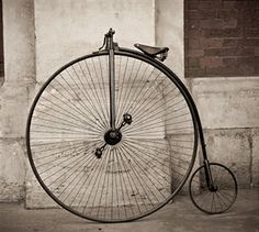 A Penny Farthing leaning against wall at Smithfield, London.