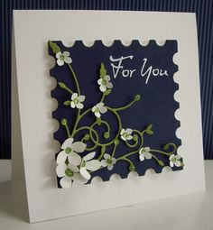 square format card...large postage stamp die cut in navy...white punched flowers on green flourishes...