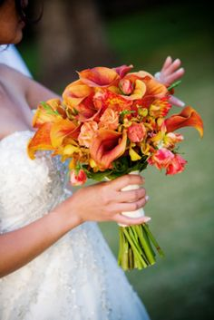 Apricot roses, orange mini calla files, white cymbidium orchids, green dendrobium orchids and seeded eucalyptus bridal bouquet.