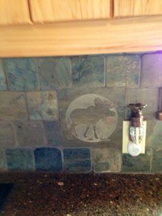 the tile backsplash in the kitchen at our cabin; it's got dear, bear, elk & moose throughout