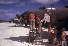 "A B-25 ground crew painting their plane.  Tarawa, 1944.  In the background is the ""Rose of SanAntone"". -"