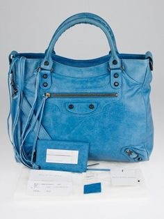 This gorgeous Balenciaga Cyclade Lambskin Leather Velo Bag from has a chic shape that is made of beautiful bright blue lambskin with incredible Classic aged brass studded hardware and leather tassel details. It also has a detachable long shoulder strap to wear this bag as a crossbody. A great bag for any stylish fashionista on-the-go. Please note, this item was originally purchased for $1395. Current retail price is $1835.