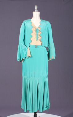 1930s turquoise colored dress with jacket.  The top of the dress is decorated with cream colored lace.  The hemline of the dress has gores at the knees and the bell shaped sleeves are scalloped at the hemline.  They are also lined with the same beige lace as the dress.  From Seneca Fashion Resource Centre.
