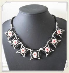 Collier ras de cou noir en capsules Nespresso recyclées. Collier composé de 7 capsules noires, roses centrales acryliques, assemblées par des anneaux. Finition perles acryliqu - 16241587