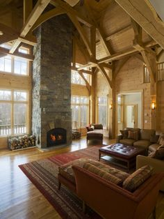 Wooden beams with a floor to ceiling exposed stone fireplace...dream family room! <3