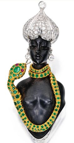 TWO-COLOR GOLD, DIAMOND AND COLORED STONE BROOCH, NARDI Designed as a snake charmer composed of carved ebony, the snake set with round and oval-shaped emeralds, with two cabochon ruby eyes, further accented by round diamonds weighing approximately 5.00 carats, signed Nardi.