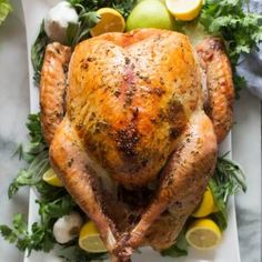 Roasted Turkey on a large white platter, garnished with lemons, apples, garlic and fresh green herbs.