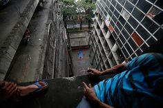 Credit: Jorge Silva/Reuters Men look down at a basketball court. The building has been called the world's tallest vertical slum