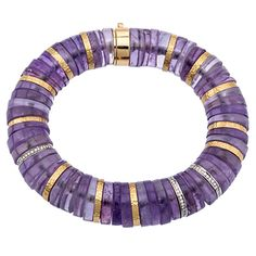 Amethyst bracelet featuring 18kt yellow and white gold. There are amethyst discs with diamond rings and hammered gold rings throughout with a large push c