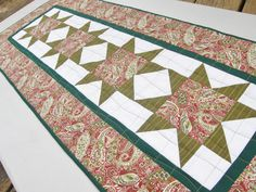 With its reds and greens this table runner is a wonderful choice for Christmas and winter decor. It was designed to be a table runner but will also be great on a side table, credenza, or dresser.    This 40 by 16 quilt is made up of four traditional Sawtooth Star Blocks, each made from moss green striped fabric for the star points, a paisley print in red and greens for the center, and a white tonal print for the background fabric. They are surrounded by a narrow inner border in solid green…
