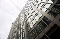low angle shot of office building against cloudy sky. - Low angle view of a tall commercial building with reflection on window against cloudy sky.