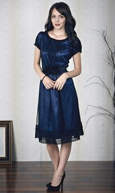 The a-line silhouette is made with a blue satin lining, which gives off a lovely sheen under the black netting. The gathers in the front and back are very flattering and elegantly hide any problem areas. The layered fringe details on the neckline, puff sleeve, and hemline add to the attention-grabbing ability of this dress. It's topped off with a gorgeous flower belt that ties in back for a perfectly fitted waist. $59.99 http://www.jenclothing.com/mi-8010-midnightblue.html