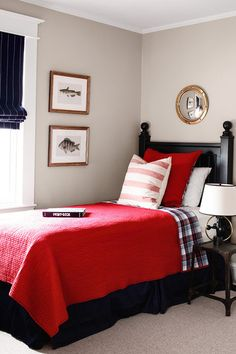 (Mirror above headboard)  Nautical-themed guest or teen boy room with red quilt, tartan and stripes, porthole mirror, and antique fish prints - ML Interiors