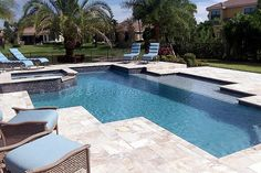 This pool offers a custom shape design with sun deck, spa and waterfall, decorative tiles and lush landscaping