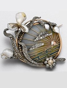 An Art Nouveau plique-à-jour enamel, diamond and pearl brooch, Ca 1900.   Depicting a rose-cut diamond sun setting over water with rose diamond clouds overhead, in a ground of blue, rose and green plique-à-jour enamel, the border decorated with a spray of irises and buds of baroque pearls and rose-cut diamonds, mounted in rose gold and silver, a glazed compartment on the back.
