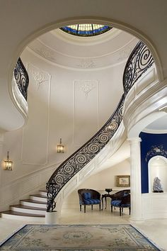 Dome in foyer, stair rail with circular pattern and wooden handrail, wood treads, floating staircase, additional molding/trim to emphasize dome, arched art niche, marble flooring