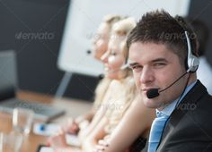 Business team in a call center ...  20s, Headsethotline, blond, board, business, businessman, businessmen, businesspeople, businesswomen, call, caucasian, centre, cheerful, company, confident, corporate, customer, executive, female, friendly, group, headphones, lMan, male, man, meeting, office, partners, partnership, positive, present, presentation, professional, screen, service, smiling, suit, team, teamwork, training, woman, young adult