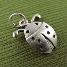 This sweet little ladybug is made of sterling silver, with a brushed satin finish. The pendant itself is about 1/2 long, which means that this is