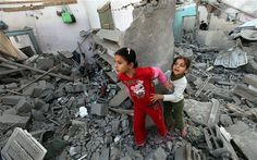 Two Palestinian youngsters look through the rubble of their destroyed house after an Israeli air strike in Beit Lahiya in the northern Gaza strip  Photo: EPA/MOHAMMED SABER