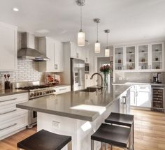 Contemporary Kitchen with Corian-solid surface countertop in dove, Pendant light, Recessed panel cabinets, Glass panel