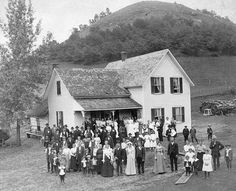 Wedding group shot....People attending a wedding reception, posing outdoors. They are standing in front of a modern house that has a log cabin attached to the back., 1890